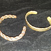 two more men's (I think?) 'cuff' type bracelets, one copper and one brass