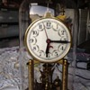 A glass dome encased brass clock the square mechanism
