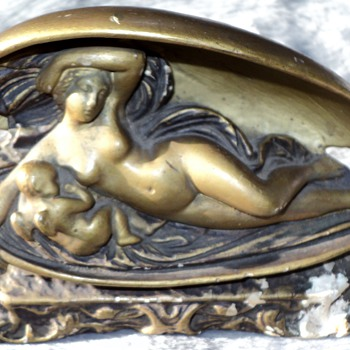 Okay I need help. It represents a woman in a coffin with a sleeping cherub - Figurines