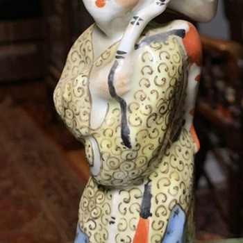 Chinese figure with a big hat and carrying a fish. - Asian