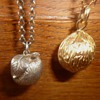 Walnut and apple pendants, one gold one silver on Belcher chain