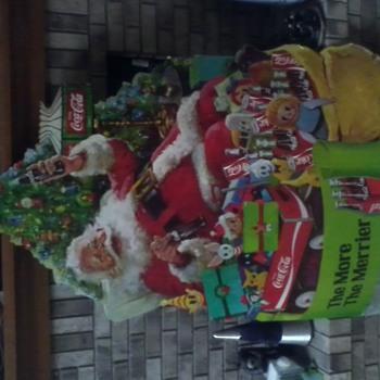 Coke Santa sitting by Christmas tree poster - Coca-Cola