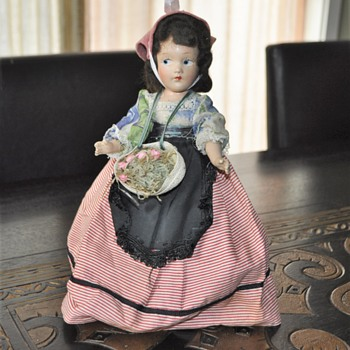 Vintage doll in a long dress and articulated body.