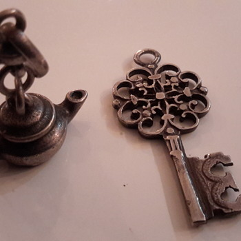 Antique key pendant and antique kettle charm in sterling silver