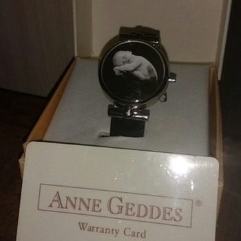 Anne Geddes Adult wrist watch, with a black and white picture of a baby on the opening cover, leather strap.
