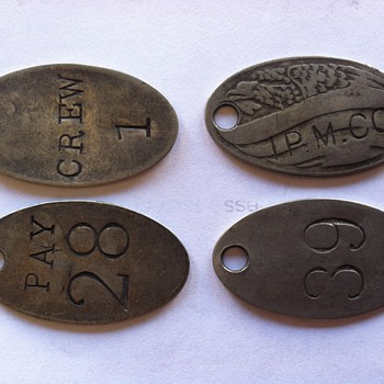 metal oval tag with number and hole in top with IPM co and an eagle - Medals Pins and Badges