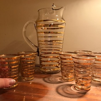 Gold-ringed slender pitcher with matching glasses