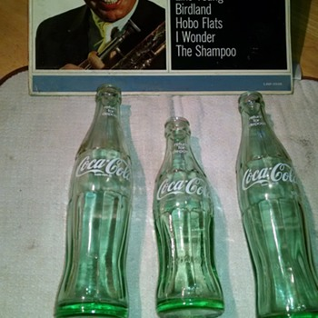 embossed on the bottom of contour COKE A COLA bottles. Many of