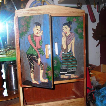 Small wooden cabinet with Asian figures on doors
