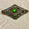 Old brooch with green stones