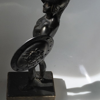 Metal sculpture of Perseus holding a shield.