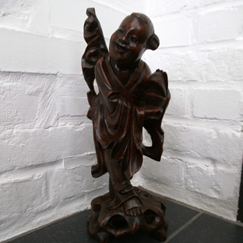 asian wooden carved smiling person (buddha?)