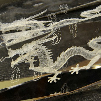 Glass thing with strange 3-dimensional dragon and clouds inside it
