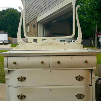 Antique dresser with decorative face above mirror