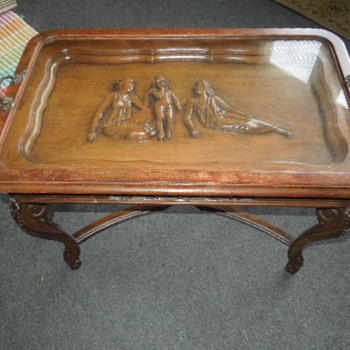 carved wooden table with glass tray on top