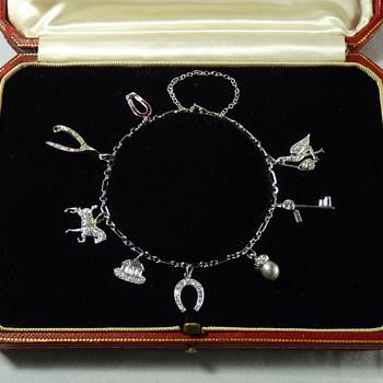 Help identifying maker of Art Deco Platinum and Diamond Charm Bracelet