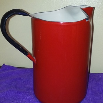 red enamelware pitcher with black handle