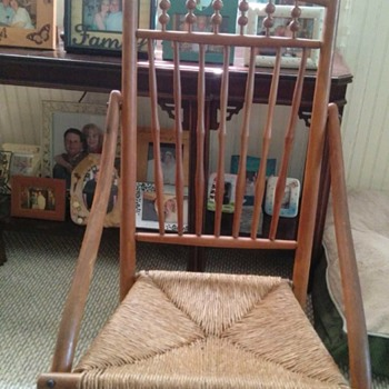 Old nursing or sewing rocker with spools / balls and has bowarm and spindles