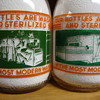 TWO MILLER DAIRY CREAM TOP QUARTS SHOWING THEIR MACHINERY ON THE BOTTLE LINE