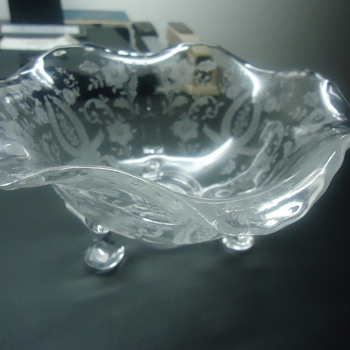 GLASS BOWL WITH ECTHEDING ON IT.