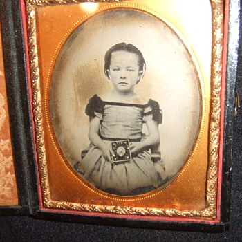 Child holds a photograph of a man