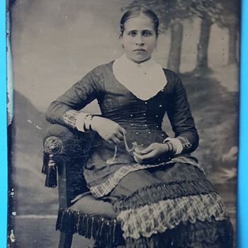 Tintype photo of Lady holding a locket or watch. - Photographs