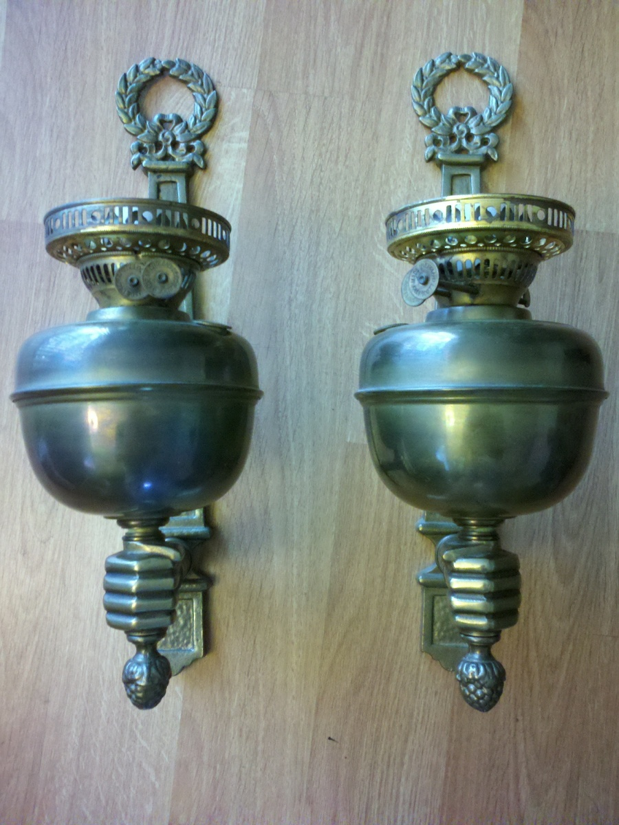 oil lamp sconce held by brass fist | Collectors Weekly
