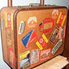 Old suitcase covered in luggage labels from all over Europe