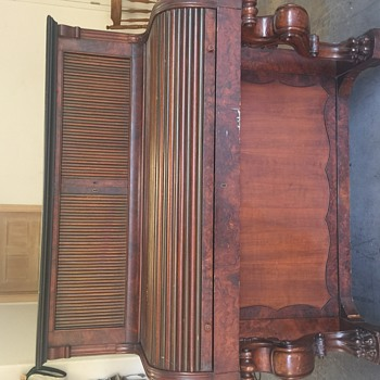 Antique roll top desk with lion paw legs.