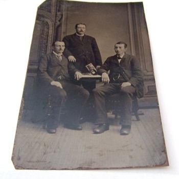 Tintype of men with stereoscope and card on table - Photographs