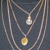 Beautiful 4 strand necklace, 1strand has clear glass cameo, 1 has locket, by Gobelle?