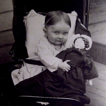 VINTAGE PHOTO OF A  BABY IN STROLLER WITH BIG CHINA HEAD DOLL.