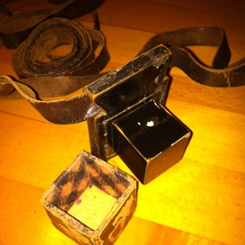 Small, black lacquer-finished wooden cube mounted on thick leather w/long strap