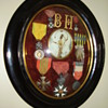 Old medals displayed in rounded glass frame.
