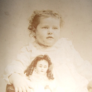 Cabinet card of a Girl holding a large doll - Photographs