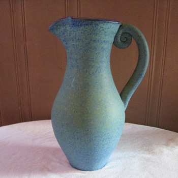 Green blue pitcher with a snail shape in the handle
