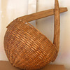 Old primitive woven basket with rounded bottom and wooden handle