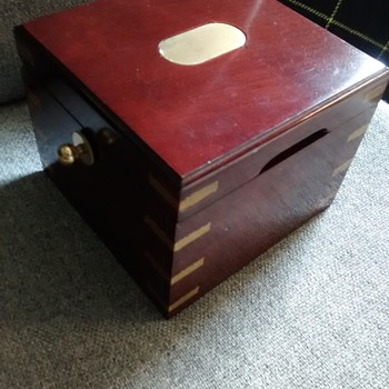 Wood and brass bound box with a centre floating revolving wood insert 16cm x 16cm x 13cm