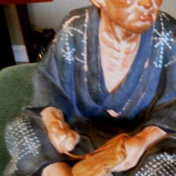 Ceramic Oriental man making shoes?