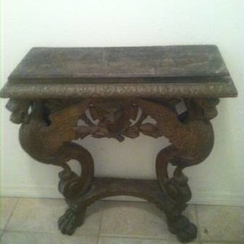 1800's griffin wall table with a lion in the middle with a branch under him