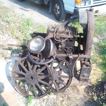 early flathead engine, with headlights , steering wheel, three tire rims