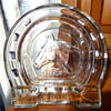 A pair of glass horseshoe ashtrays with etched horsehead