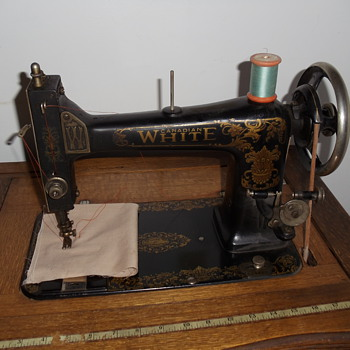 White treadle sewing machine in oak cabinet