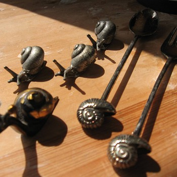 Silver snails, seperately and on a spoon and fork.  - Animals