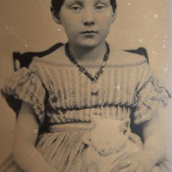 Tintype of girl holding a sleeping kitten - Photographs
