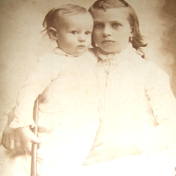Cabinet card of two children with one holding a hammer