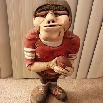 1973 statue of a comical football player - not sure of the artist's signature