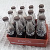 Miniature Coca cola bottles and crate.