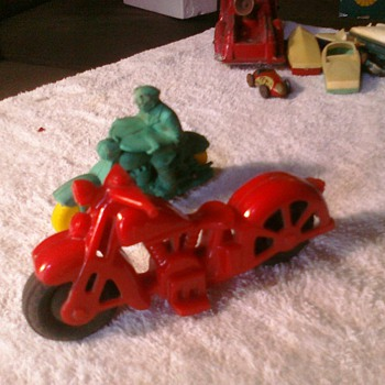 Old toy motorcycles.  The red is a hard plastic Harley or Indian and the other is most likely an Auburn Rubber toy - Model Cars