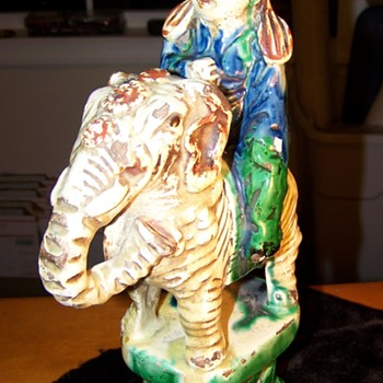 Antique statue man riding elephant with animal on his head?????